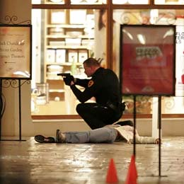 A Salt Lake City Police officer squats with his gun drawn next to a body inside the Trolley Square Mall Monday night. Six people, including the gunman, died from the shooting. (Mike Terry, Deseret Morning News)